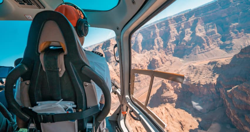 A pilot drives a helicopter over the Grand Canyon on a sunny day
