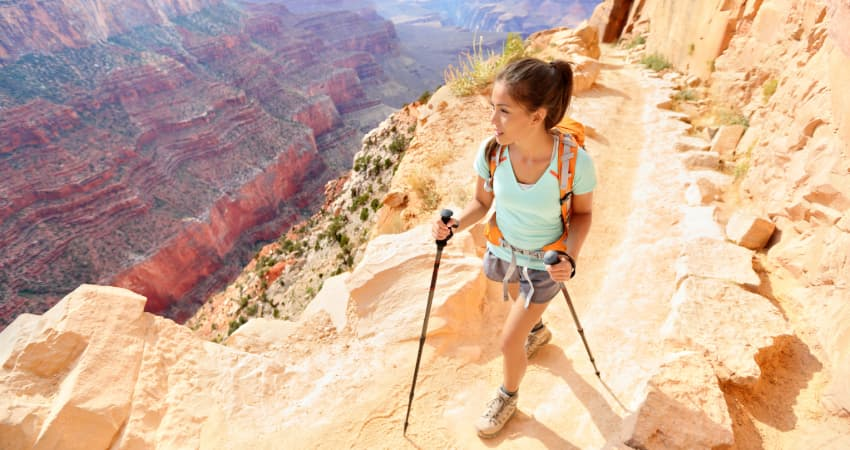 A woman hikes into the Grand Canyon with a backpack and hiking poles