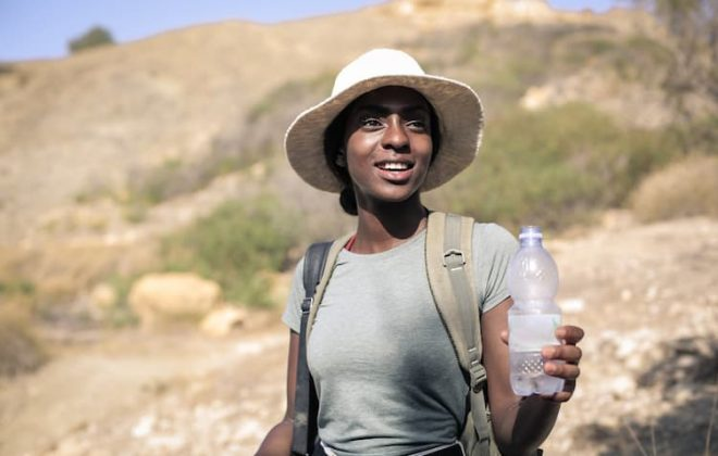 Woman in desert with water bottle