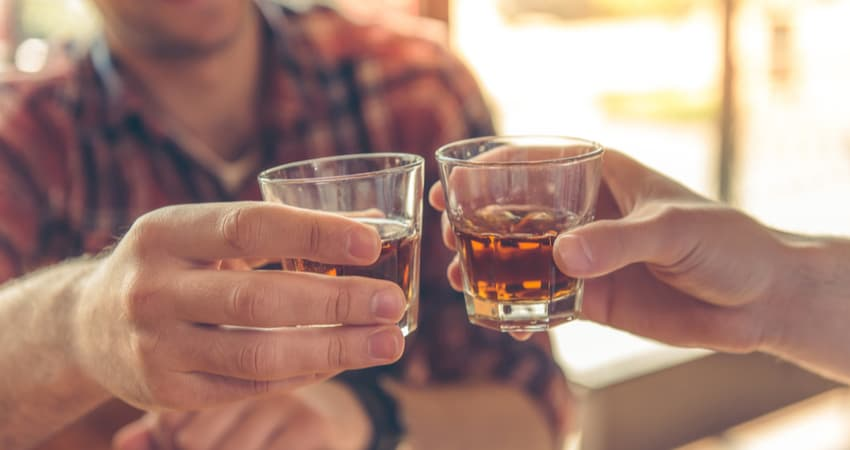 Two friends toasting whiskey samples