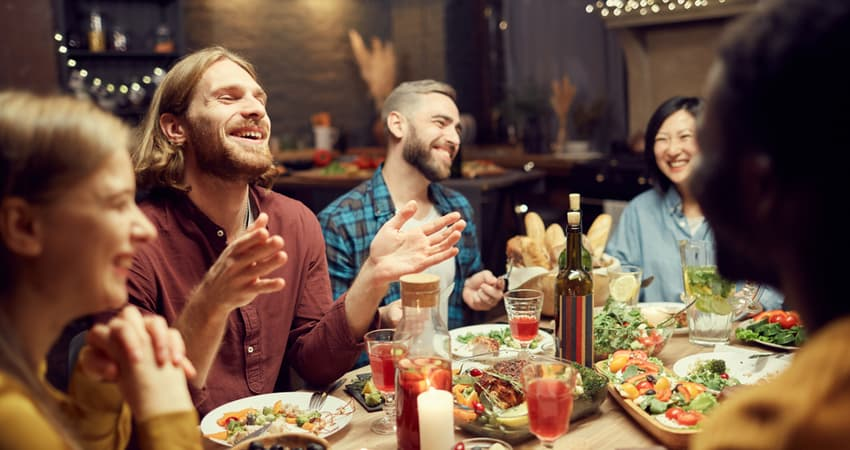 A group of friends smiling and laughing at a restaurant