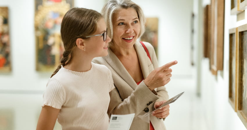 A teen and an adult admire paintings in an art museum