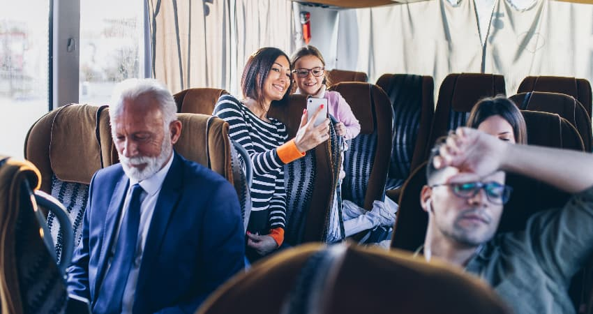 A group of people relax on a charter bus rental during a road trip