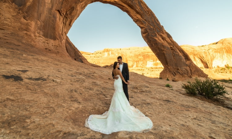 bride and groom pose under a red rock natural arch